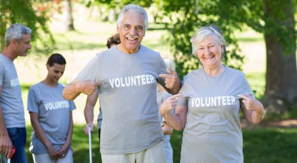 Happy volunteer senior couple smiling at the camera on a sunny d